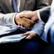 Geschäftsmänner im Anzug schütteln sich die Hände.