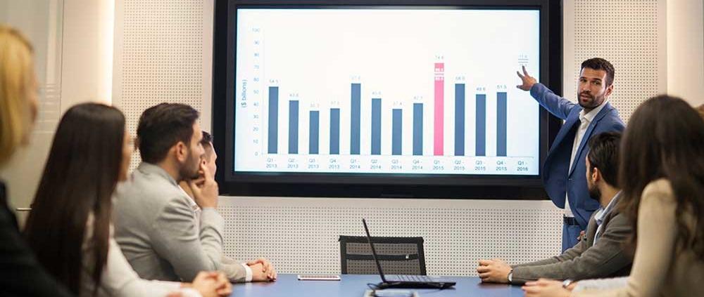 Ein junger Geschäftsmann hält eine Präsentation vor seinen Kollegen und zeigt auf eine Leinwand.