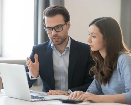Geschäftsmann erklärt jüngerer Mitarbeiterin etwas an ihrem Laptop.