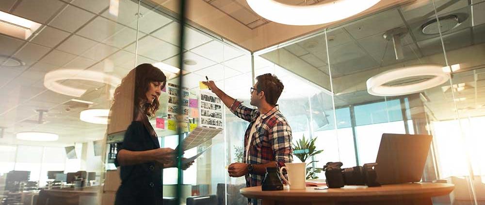 Zwei junge Geschäftsleute arbeiten zusammen in einem Büro und stehen vor einer Glaswand mit Post Its.