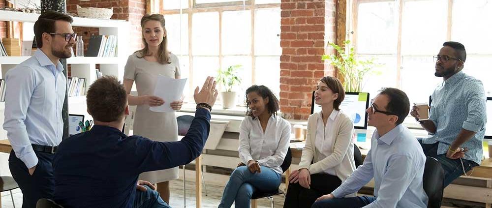 Frau gibt eine PowerPoint Schulung, ein Mann hebt seine Hand um eine Frage zu stellen.